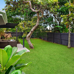 This is an example of a beach style backyard garden in Sunshine Coast with concrete pavers.