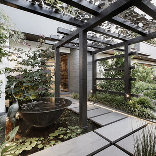 Inspiration for an industrial front yard partial sun garden in Melbourne with with pond and concrete pavers.