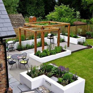 Moderner Garten hinter dem Haus mit Dielen und Hochbeet in London