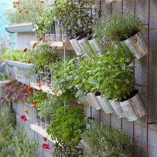 Inspiration för en liten funkis gårdsplan i full sol som tål torka på våren, med en fontän och marksten i betong