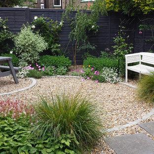 Cette image montre un petit jardin à la française arrière traditionnel au printemps avec une entrée ou une allée de jardin, une exposition ombragée et des pavés en pierre naturelle.