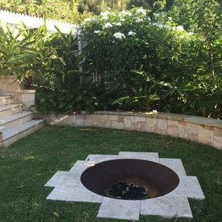 Idéer för att renovera en mellanstor tropisk trädgård i delvis sol, med naturstensplattor och en öppen spis