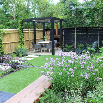 This is an example of a small contemporary partial sun backyard formal garden in Hampshire with decking for summer.