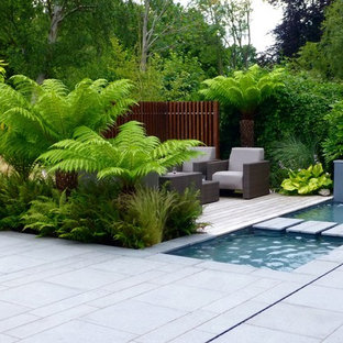 Design ideas for a medium sized contemporary back full sun garden for summer in London with a water feature and natural stone paving.