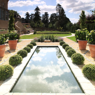 Mediterranean formal full sun garden for summer in Other with a pond and gravel.