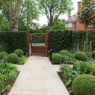 Design ideas for a traditional front formal partial sun garden for summer in London with natural stone paving.