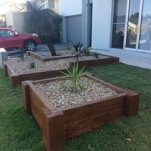 This is an example of a mid-sized traditional partial sun front yard stone formal garden in Brisbane.