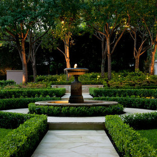 This is an example of a traditional backyard partial sun formal garden for summer in Sydney with a water feature and natural stone pavers.