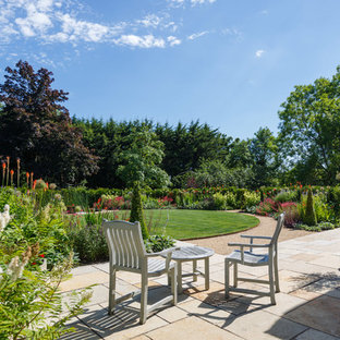 Photo of a large classic back full sun garden in Gloucestershire with natural stone paving.
