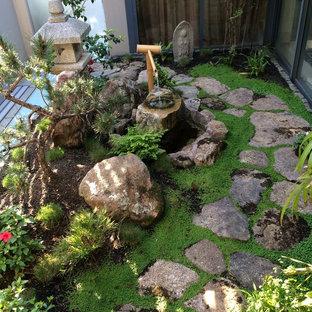 Immagine di un piccolo giardino etnico in ombra sul tetto in primavera con pavimentazioni in pietra naturale