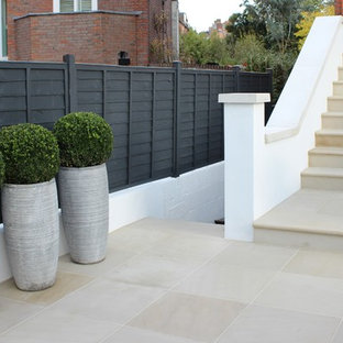 Photo of a medium sized contemporary front full sun garden in London with a garden path and natural stone paving.