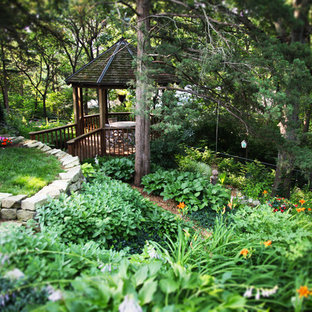 This is an example of a large rustic partial sun backyard stone landscaping in Other for summer.