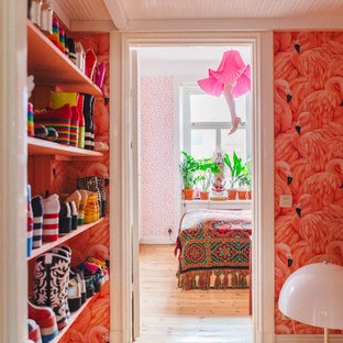 Eclectic gender-neutral walk-in wardrobe in Stockholm with open cabinets and light hardwood floors.