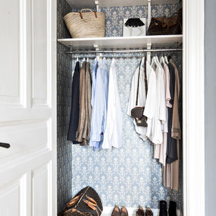 Photo of a small traditional gender-neutral walk-in wardrobe in Gothenburg with painted wood floors and white floor.