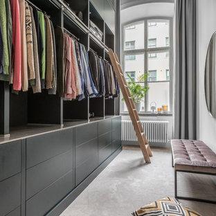 Inredning av ett klassiskt stort walk-in-closet för könsneutrala, med öppna hyllor, svarta skåp, heltäckningsmatta och beiget golv