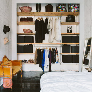 Photo of a mid-sized scandinavian gender-neutral built-in wardrobe in Stockholm with open cabinets, painted wood floors, light wood cabinets and black floor.