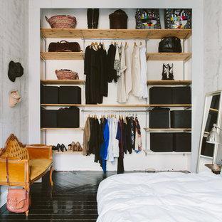 Idée de décoration pour un placard dressing nordique de taille moyenne et neutre avec un placard sans porte, un sol en bois peint, des portes de placard en bois clair et un sol noir.