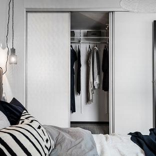 Foto de armario unisex, nórdico, de tamaño medio, con armarios con paneles lisos, puertas de armario blancas, suelo de madera clara y suelo gris