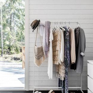 Ejemplo de armario y vestidor de mujer, escandinavo, pequeño, con armarios abiertos, suelo de madera oscura y suelo negro