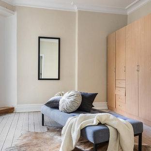 Inredning av ett skandinaviskt omklädningsrum för könsneutrala, med släta luckor, skåp i ljust trä, bambugolv och beiget golv