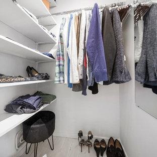 Nordisk inredning av ett walk-in-closet för könsneutrala, med öppna hyllor, vita skåp, ljust trägolv och beiget golv