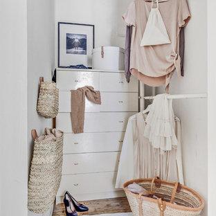 Bild på ett litet minimalistiskt walk-in-closet för kvinnor, med öppna hyllor, vita skåp, ljust trägolv och brunt golv