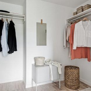 Inspiration för ett minimalistiskt walk-in-closet för könsneutrala, med ljust trägolv och beiget golv