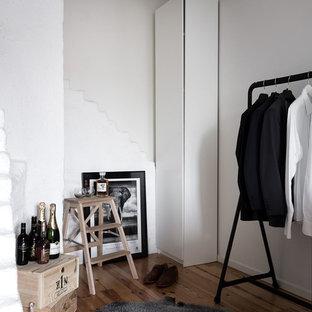 Bild på ett mellanstort minimalistiskt omklädningsrum för könsneutrala, med släta luckor, vita skåp, ljust trägolv och brunt golv