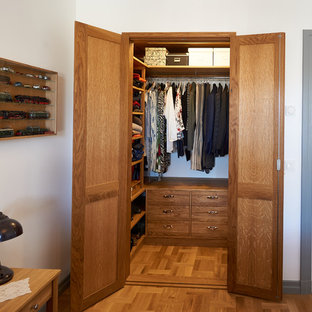 Design ideas for a small midcentury gender-neutral walk-in wardrobe in Stockholm with open cabinets, medium wood cabinets and medium hardwood floors.