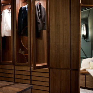 Immagine di una cabina armadio per donna moderna di medie dimensioni con ante in legno scuro, moquette e pavimento rosa