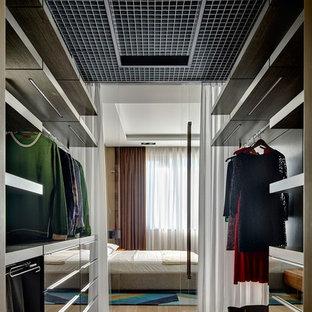 На фото: гардеробные комнаты в современном стиле с плоскими фасадами, паркетным полом среднего тона и коричневым полом для женщин или мужчин