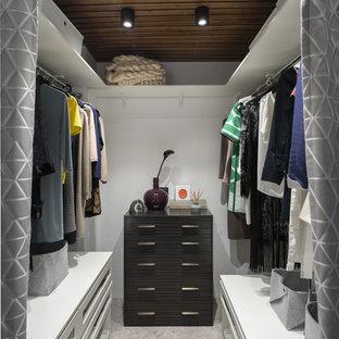 На фото: гардеробная комната в морском стиле с белыми фасадами, ковровым покрытием, серым полом и открытыми фасадами для женщин