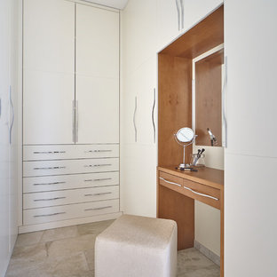 Photo of a contemporary gender neutral dressing room in Other with flat-panel cabinets, white cabinets and grey floors.