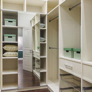 Foto på ett funkis walk-in-closet för könsneutrala, med öppna hyllor, vita skåp och mörkt trägolv