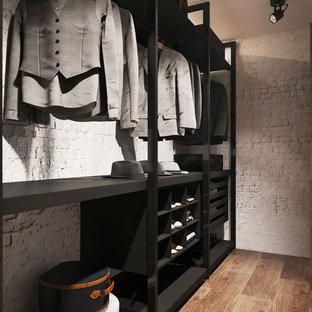 バルセロナの中くらいの男女兼用コンテンポラリースタイルのおしゃれなウォークインクローゼット (オープンシェルフ、黒いキャビネット、磁器タイルの床、茶色い床) の写真