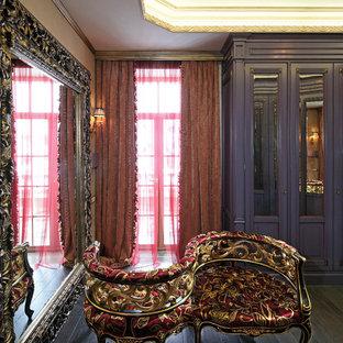 モスクワの大きい男女兼用ヴィクトリアン調のおしゃれなウォークインクローゼット (無垢フローリング、茶色い床) の写真