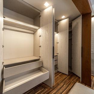 Foto de armario unisex, asiático, pequeño, con armarios con paneles lisos, puertas de armario de madera clara, suelo de madera en tonos medios y suelo marrón