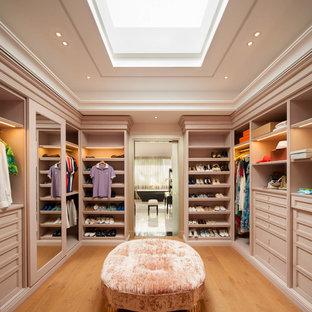 Modelo de armario vestidor unisex, actual, grande, con puertas de armario beige, suelo de madera en tonos medios y armarios con paneles empotrados