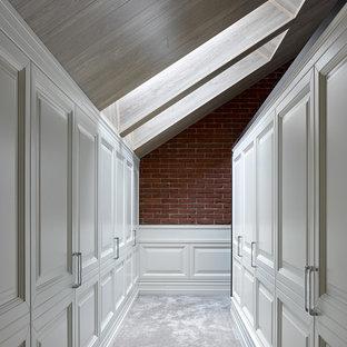 На фото: гардеробные комнаты в стиле современная классика с белыми фасадами, ковровым покрытием, серым полом и фасадами с выступающей филенкой для женщин или мужчин
