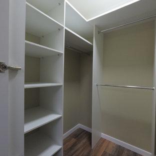 Modelo de armario vestidor unisex, tradicional renovado, de tamaño medio, con armarios con puertas mallorquinas, puertas de armario blancas, suelo laminado y suelo marrón