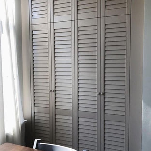 Photo of a mid-sized transitional built-in wardrobe in Other with louvered cabinets and beige cabinets.