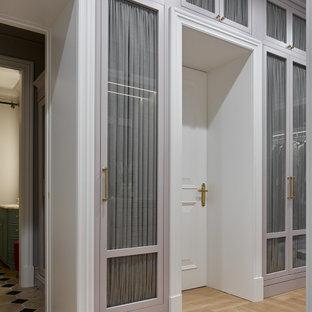 Modelo de armario vestidor unisex, contemporáneo, grande, con armarios tipo vitrina, puertas de armario grises, suelo de madera clara y suelo amarillo