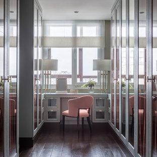 На фото: большая парадная гардеробная в стиле современная классика с стеклянными фасадами, серыми фасадами, темным паркетным полом и коричневым полом для женщин
