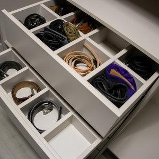 Imagen de armario y vestidor unisex, de tamaño medio, con armarios con paneles lisos, puertas de armario beige, suelo laminado y suelo gris