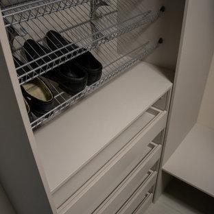 Diseño de armario y vestidor unisex, de tamaño medio, con armarios con paneles lisos, puertas de armario beige, suelo laminado y suelo gris