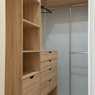 Foto de armario vestidor pequeño con armarios con paneles lisos, puertas de armario de madera clara, suelo de baldosas de porcelana y suelo gris