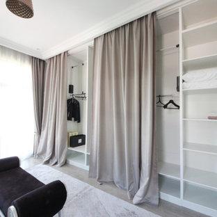 Foto de armario vestidor de mujer, ecléctico, grande, con armarios abiertos, puertas de armario de madera clara, suelo de madera en tonos medios y suelo beige