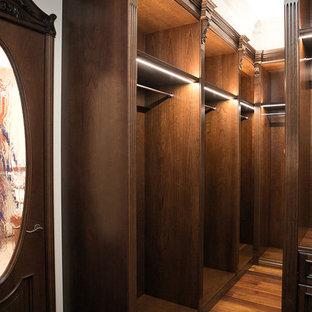 Foto de armario vestidor unisex, tradicional, pequeño, con armarios con rebordes decorativos, puertas de armario de madera en tonos medios y suelo de madera oscura