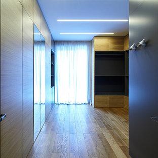 Imagen de armario vestidor unisex, contemporáneo, grande, con puertas de armario de madera oscura, suelo laminado y suelo beige