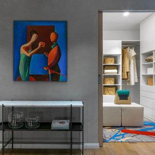 Стильный дизайн: маленькая гардеробная комната унисекс в современном стиле с белыми фасадами, ковровым покрытием, разноцветным полом и плоскими фасадами - последний тренд